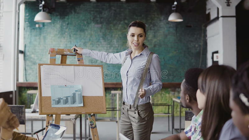 Meeting of mixed race business team. Woman manager presenting financial data to group of people at modern office. Female team leader using graphs and board royalty free stock photos