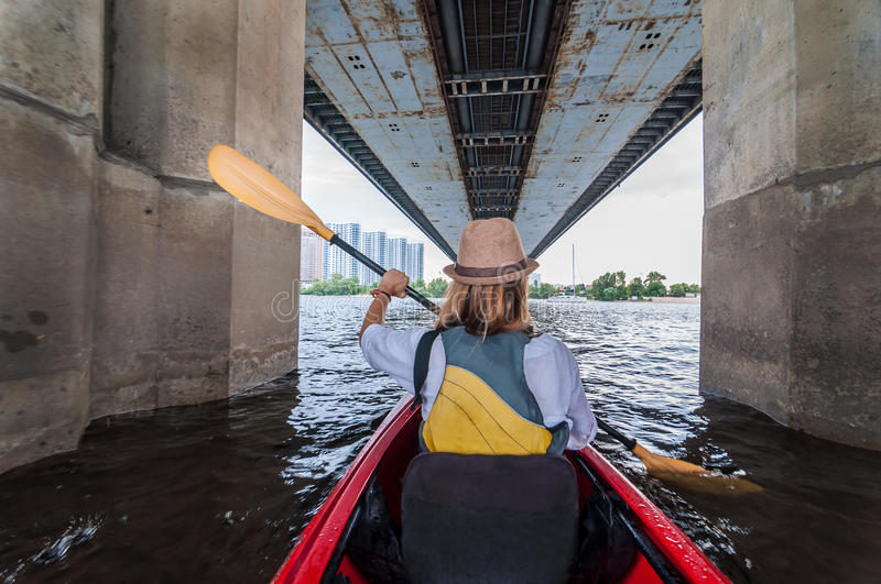Meeting morning on kayaks. Rear view of young girl kayaking bu the river and under the bridge. Urban exploration concept stock photography