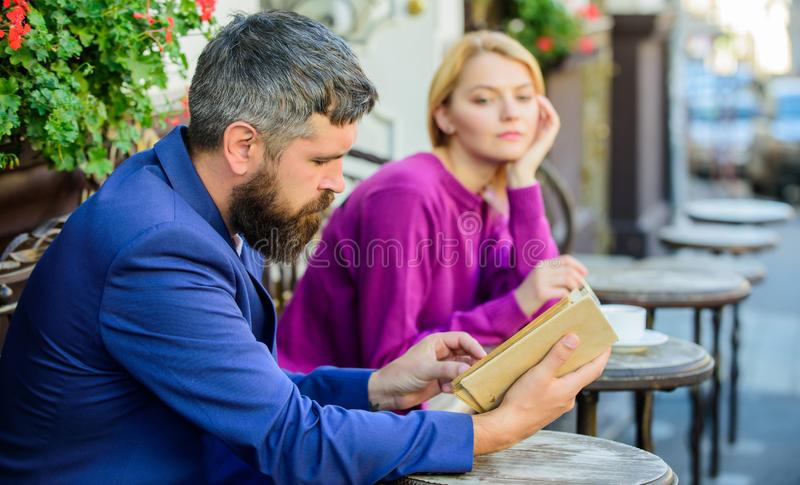 Meeting people with similar interests. Man and woman sit cafe terrace. Girl interested what he reading. Literature. Meeting people with similar interests. Man royalty free stock images