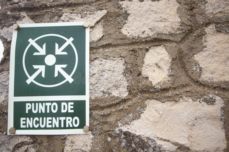 Meeting point sign attached to stone wall. Spanish languaje letter stock photography