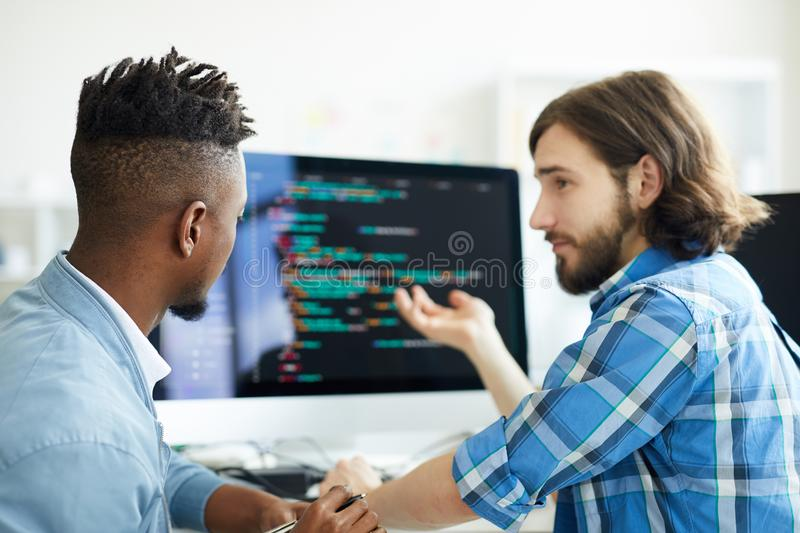 Meeting of programmers. One of software developers pointing at computer screen while explaining his co-worker new method of data decoding stock photo