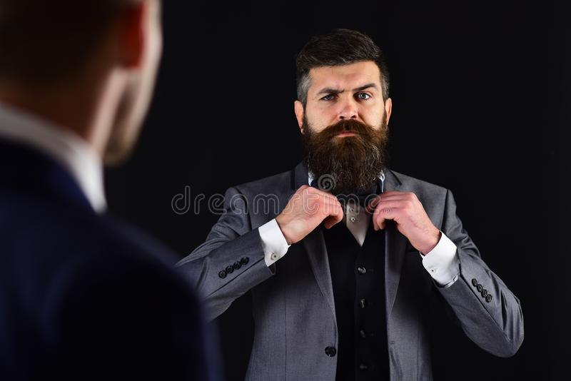 Meeting of reputable businessmen, black background. Man with beard on serious face, ties bow tie before meeting stock photo