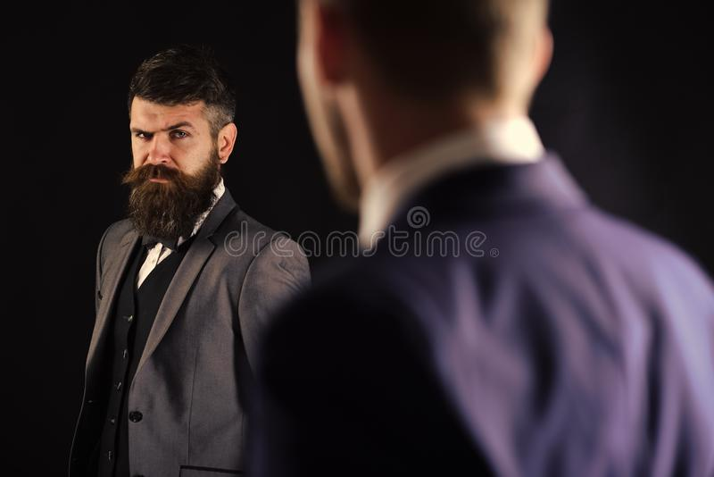 Meeting of reputable businessmen, black background. Man with beard on suspicious face, and shoulders of partner stock photos