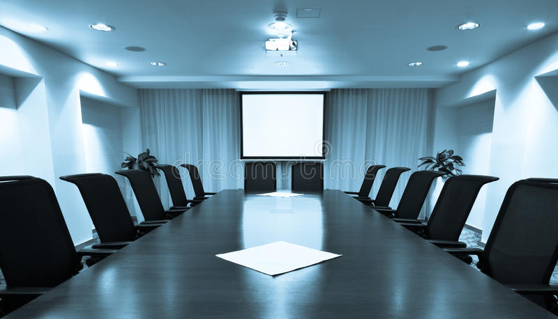 Meeting room. Empty meeting room with blank projector screen royalty free stock photography