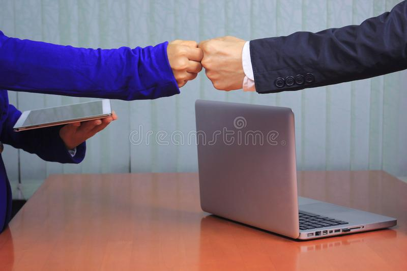 Meeting teamwork concept,Friendship,Two Business people giving fist bump after successful negotiations at office stock photos
