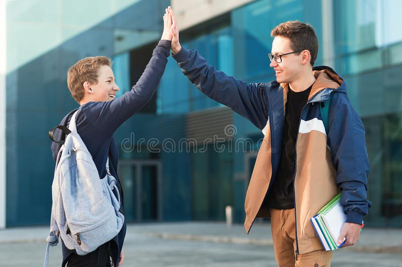 Meeting of two smiling teenage friends outdoors royalty free stock photo