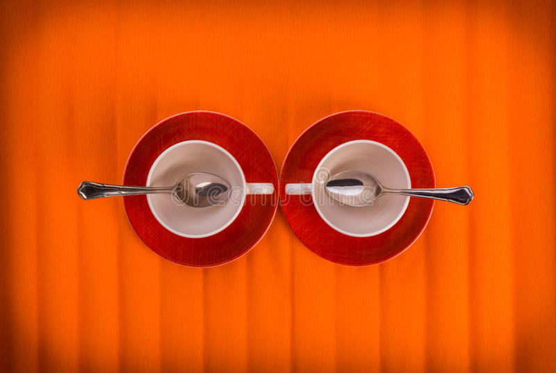 Meeting- two white empty cups with tea spoons, on red plates over orange color background, view from above. Composition of two small white color cups with silver stock image