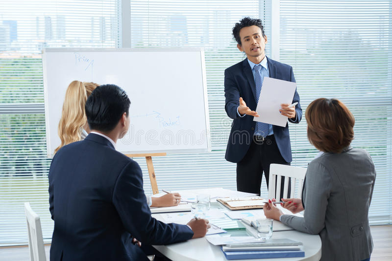 Meeting. Vietnamese entrepreneur talking to coworker during presentation stock photos