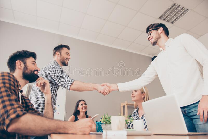 At a meeting young businessmen shake hands to each other.  stock photos
