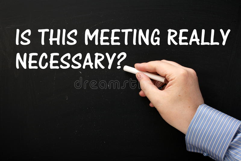 Meetings and Productivity Concept. Male hand wearing a business shirt writing the question Is This Meeting Really Necessary on a blackboard stock photography