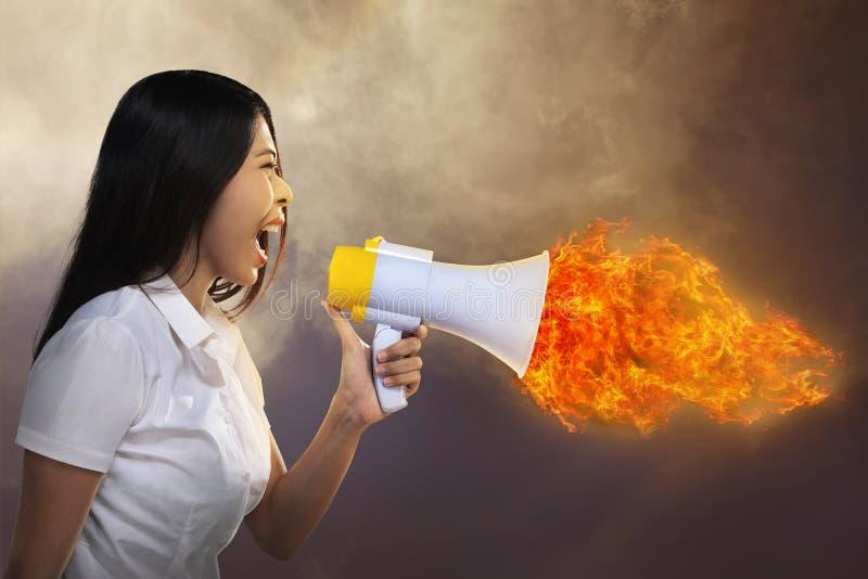 Megáfono de grito de la mujer asiática en el fuego fotos de archivo libres de regalías