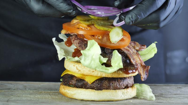 Mega big burger with a double cutlet with vegetables and a sesame bun, the process of forming a burger, the chef in royalty free stock images