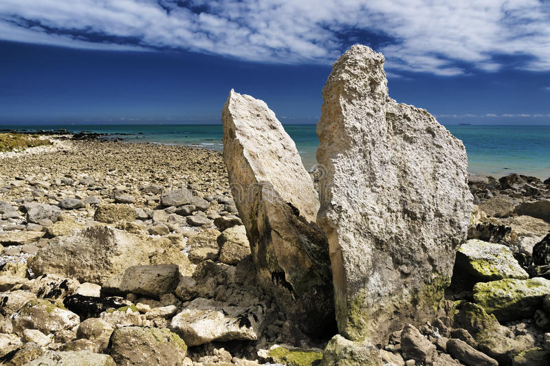 Megalith on dover coastline UK. Free standing rocks that point upwards into the clouds under the cliffs at samphire hoe stock images
