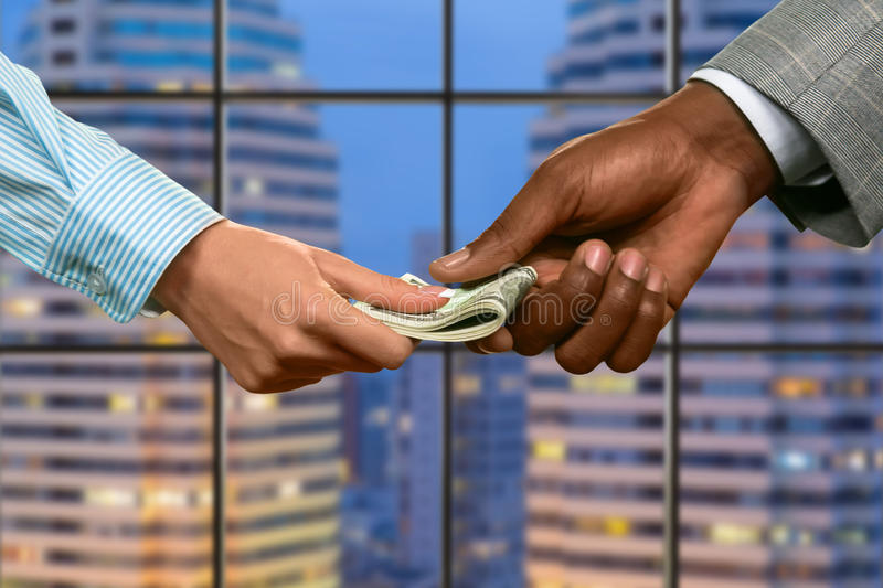 Megalopolis business couple passing money. Officeman gives woman her salary. Right invesment to make. Money is the best motivation stock photography