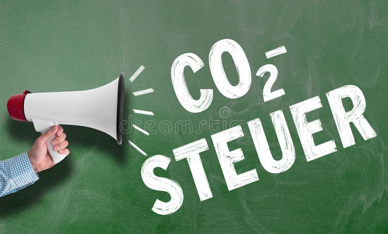 Megaphone εκμετάλλευσης χεριών ή bullhorn ενάντια στον πίνακα κιμωλίας με το κείμενο CO2-STEUER, γερμανικά για το φόρο άνθρακα στοκ εικόνα