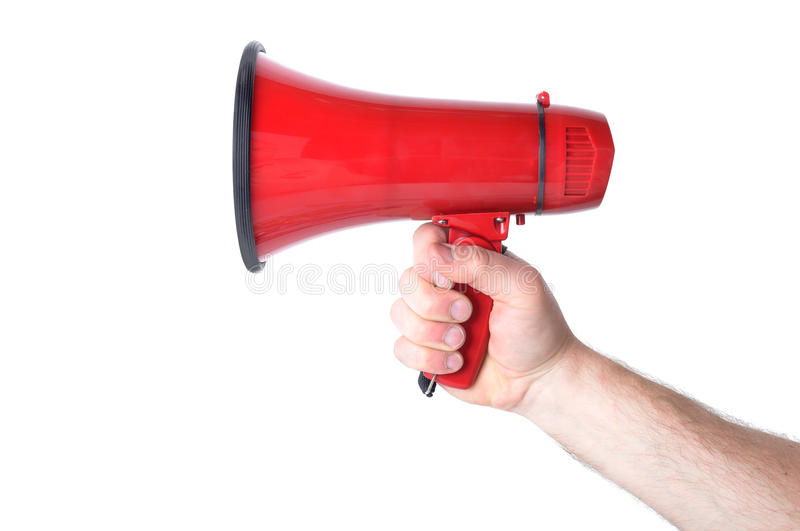 Megaphone. Hand holding a red Megaphone isolated on white royalty free stock photo