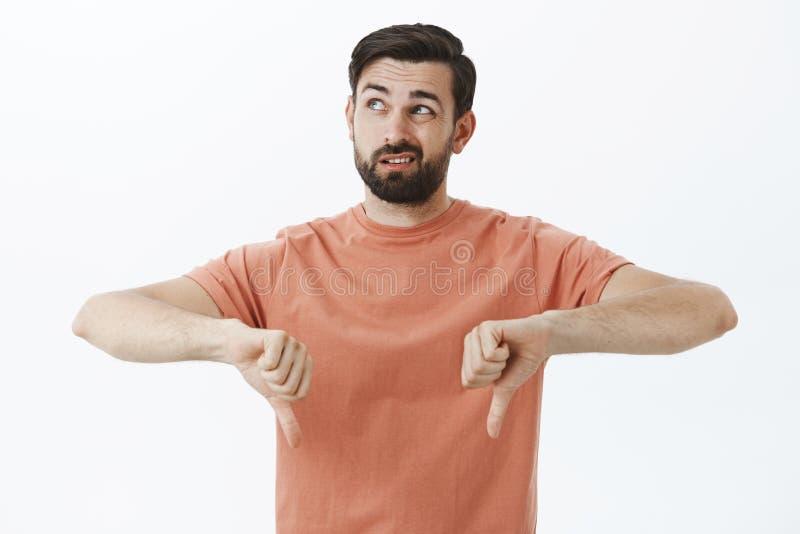 Meh ja był okropny Nierad i nieporuszony atrakcyjny brodaty 30s mężczyzna patrzeje do kryjówki w różowej koszulce przygląda się p obrazy stock