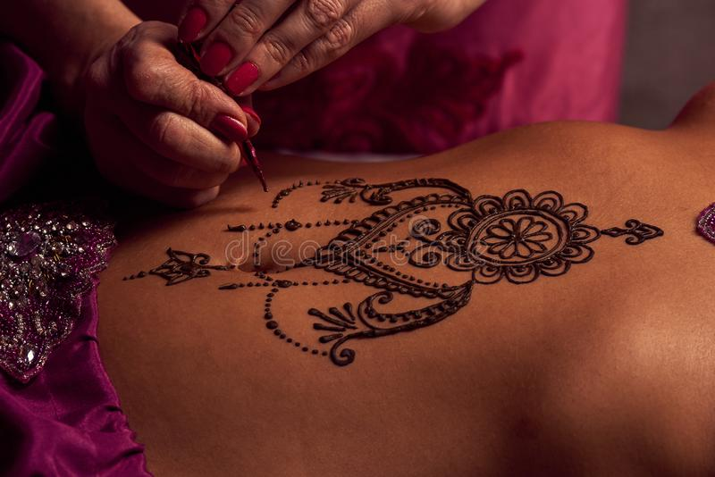 Mehendi artist paints an ornament of henna on an eastern beautiful girl's stomach. White women a mehendi artist paints an ornament of henna on an eastern stock images