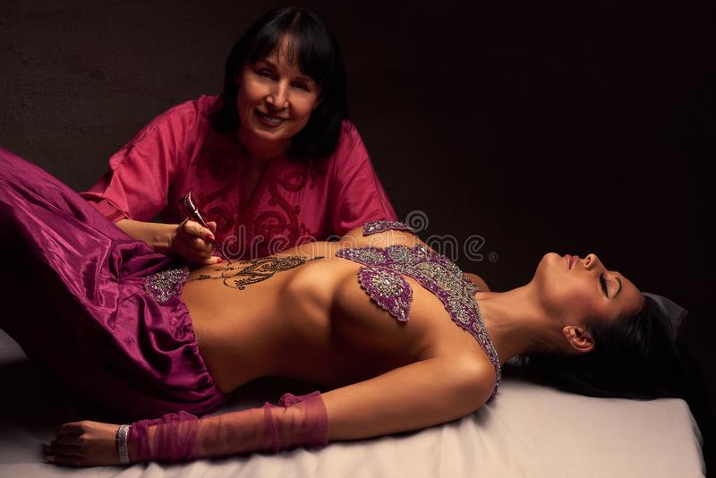 Mehendi artist paints an ornament of henna on an eastern beautiful girl's stomach. White women a mehendi artist paints an ornament of henna on an eastern stock photography