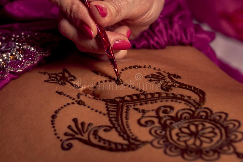 Mehendi artist paints an ornament of henna on an eastern beautiful girl's stomach. White women a mehendi artist paints an ornament of henna on an eastern royalty free stock image