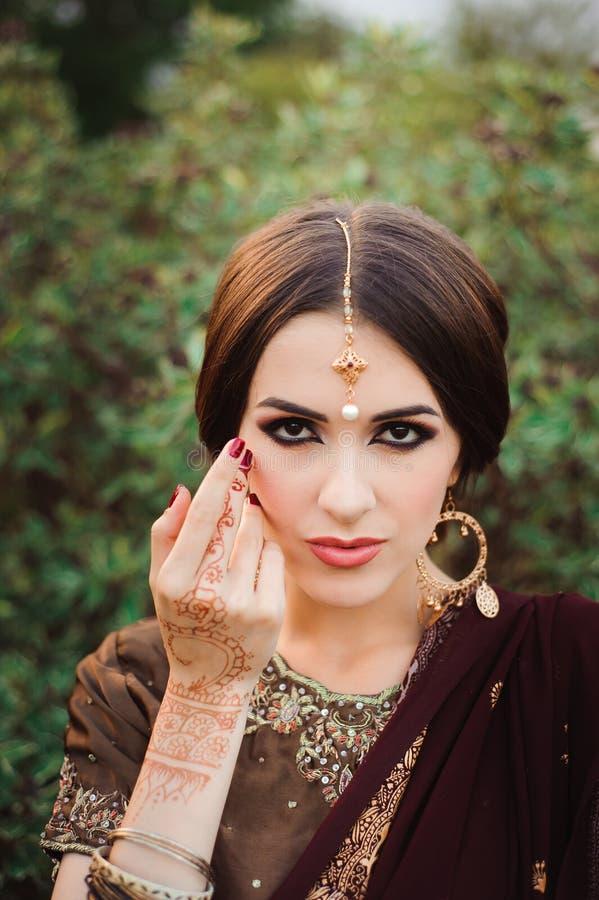 Mehendi en las manos de las muchachas, manos de la mujer con el tatuaje marrón del mehndi Manos de la muchacha india de la novia  foto de archivo libre de regalías