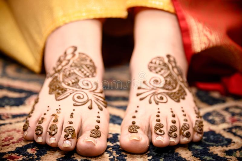 Mehendi Rasm. A woman`s feet with mehendi at the time of mehendi celebration during marriage royalty free stock image