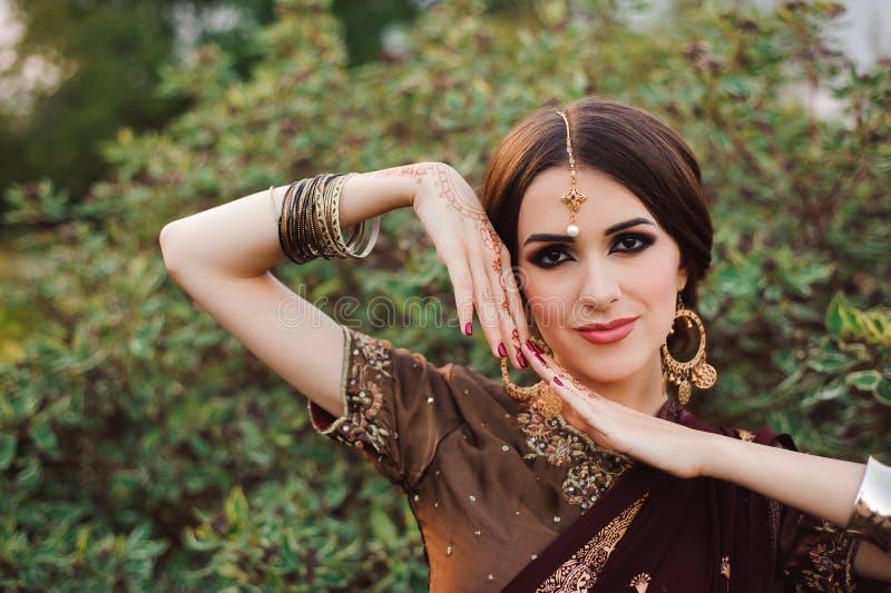 Mehendi sur les mains des filles, mains de femme avec le tatouage brun de mehndi Mains de fille indienne de jeune mariée avec les photos stock