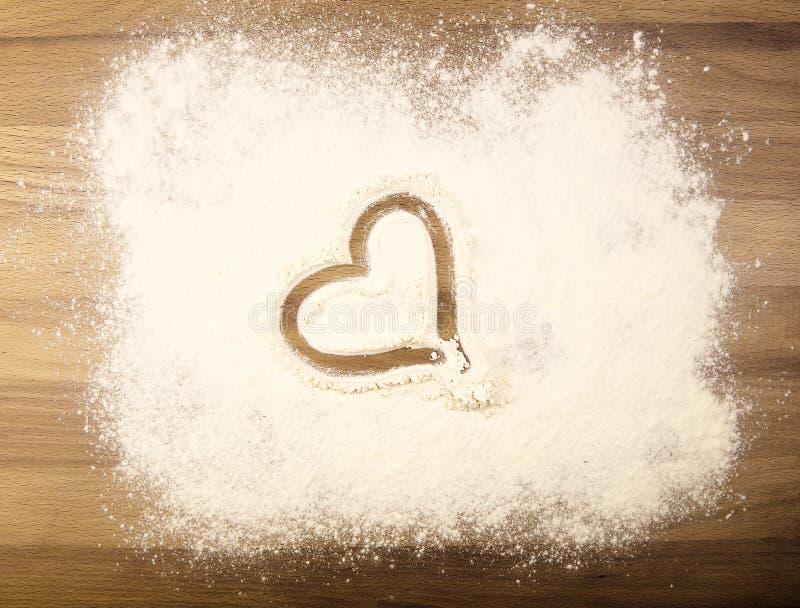 Mehl auf dem Tisch mit Herzen lizenzfreies stockfoto