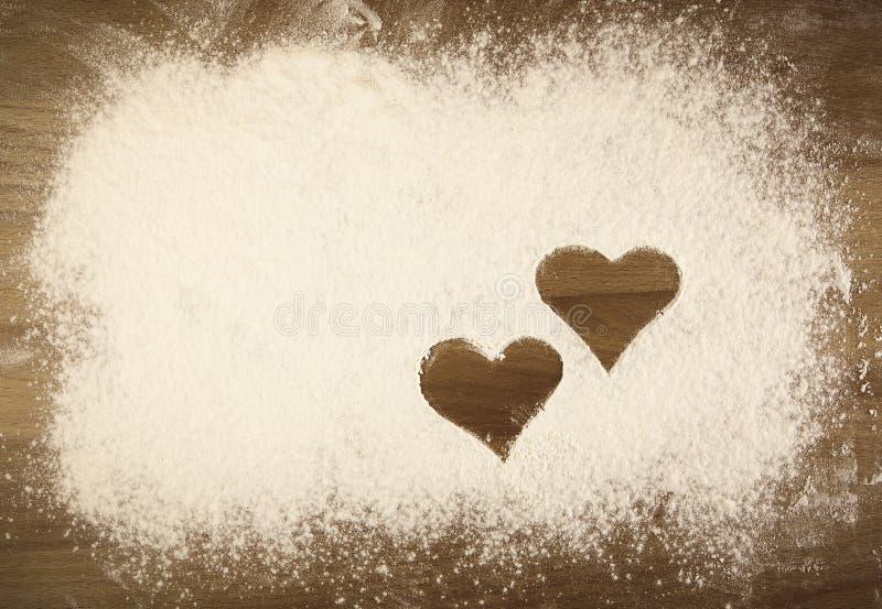 Mehl auf dem Tisch mit Herzen stockfoto