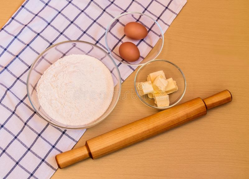 Mehl, Eier, Butter und Nudelholz auf Tabelle stockfotografie