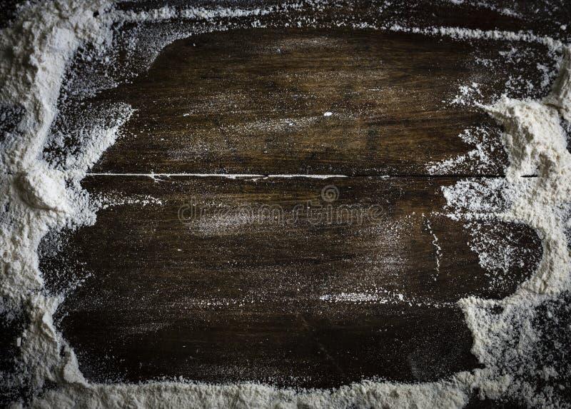 Mehl zerstreute auf einen Holztisch lizenzfreies stockbild