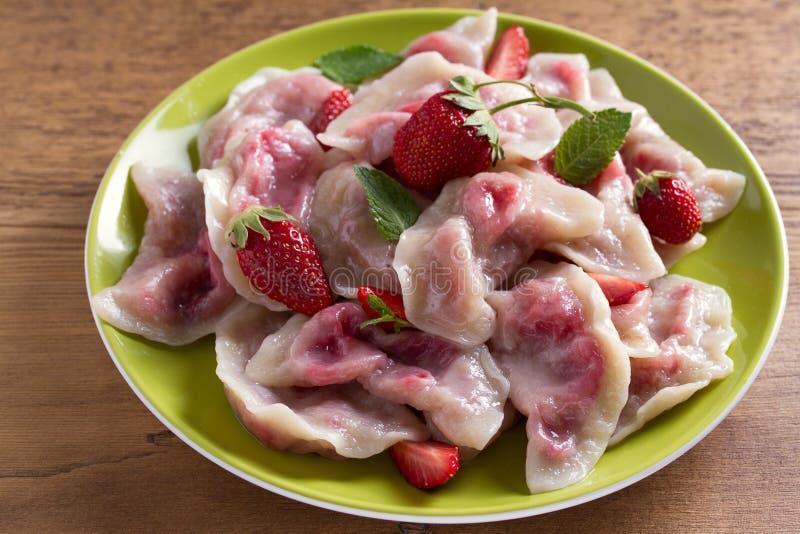 Mehlklöße, gefüllt mit Erdbeeren Pierogi, varenyky, vareniki, pyrohy - Mehlklöße mit dem Füllen stockfotografie