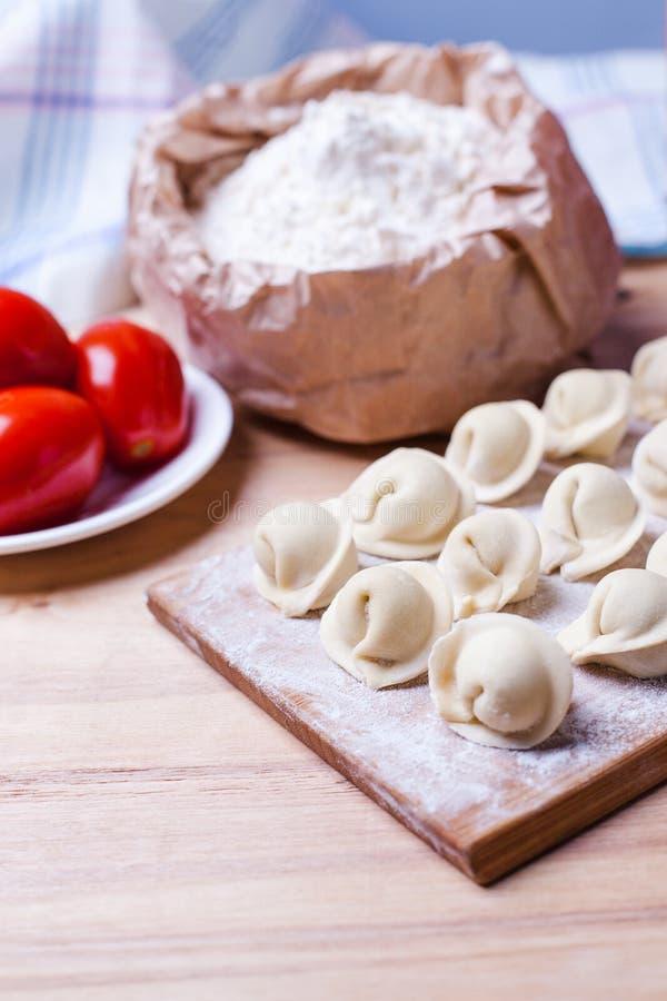 Mehlklöße mit Fleisch auf einem hölzernen Stand - kochend, rohe ungeschälte Mehlklöße, nationaler Russe, ukrainische Küche stockfotografie