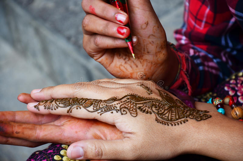Mehndi or Henna india style at Nepal. Mehndi or Henna is a paste that is bought in a cone shaped tube and is made into designs for men and women. It is also stock photography