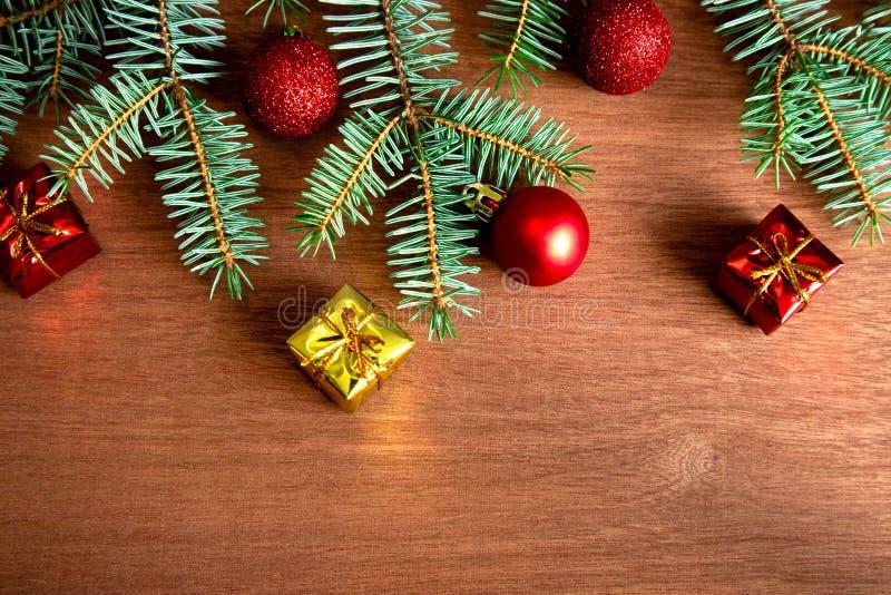 Mehrere grüne Fichtenzweige mit roten Weihnachtsbällen, Weihnachtsbaumdekorationen und kleinen Geschenken auf Holzfußboden flach stockfoto