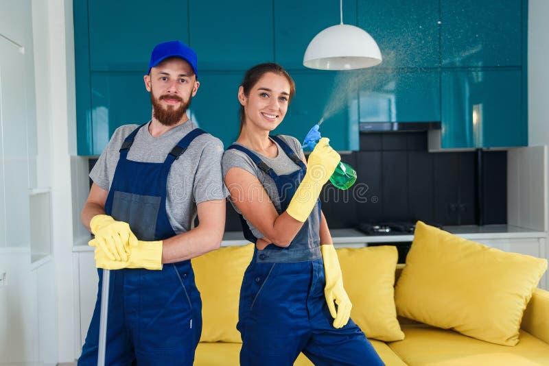 Mehrere professionelle Reiniger kommen in der modernen Küche mit Waschmitteln zusammen Hausreinigung stockfoto