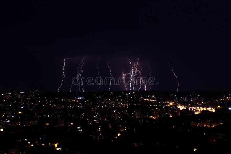 Mehrfache Blitzschläge über einer Großstadt bis zum Nacht stockfoto