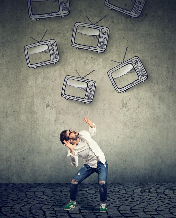 Mehrfache Fernseher, die auf einen strssed erschrockenen Mann fallen stockfotografie