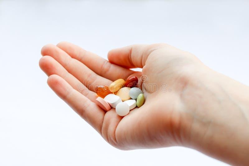 Mehrfachverbindungsstelle färbt Pillen in der Hand auf weißem Hintergrund Nehmen Sie Ihre Medizin und Vitamine lizenzfreie stockfotografie