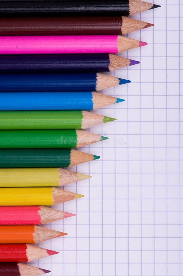 Mehrfarbenbleistifte auf Papier stockbilder