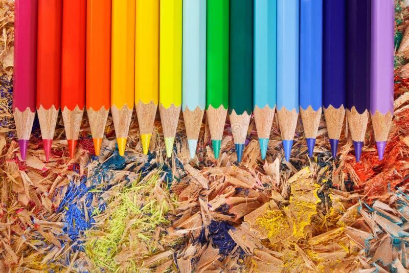 Mehrfarbenbleistifte raibow auf den Schnitzeln stockfoto