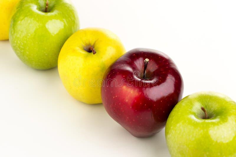Mehrfarbige Äpfel in Folge auf einer weißen Tabelle lizenzfreie stockfotos