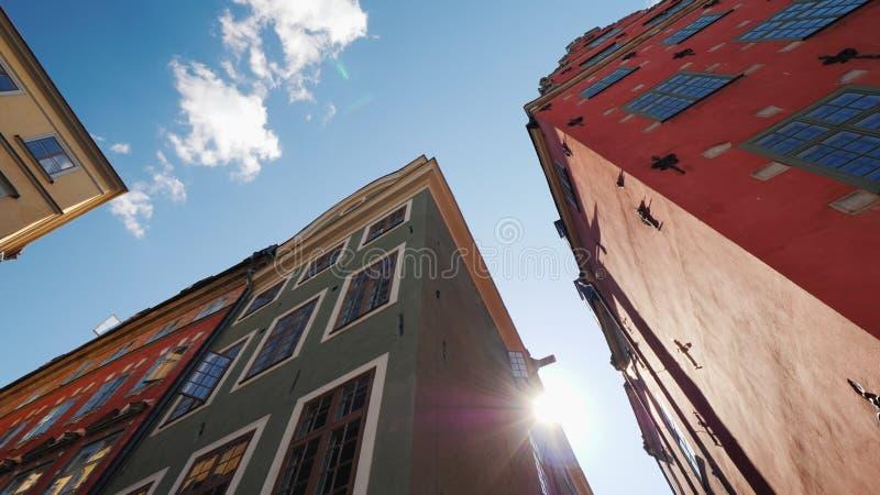 Mehrfarbige alte Häuser in Stockholm Schöne europäische Architektur, die Sonne glänzt von hinten das Dach des Hauses lizenzfreie stockbilder