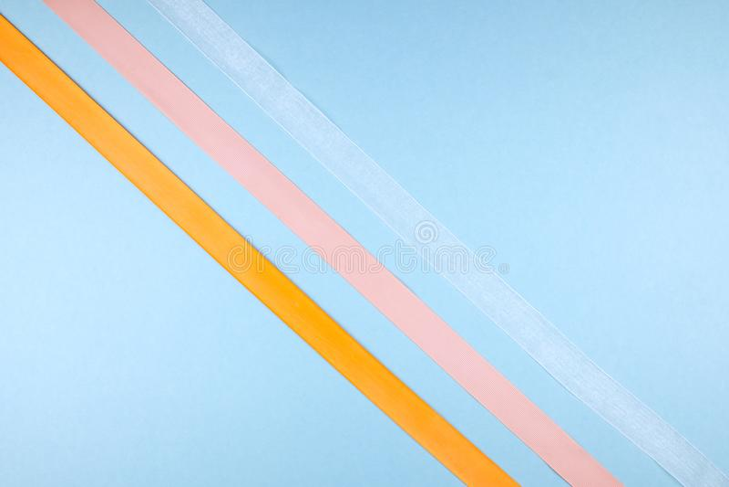 Mehrfarbige Bänder auf einem blauen Hintergrund Minimalismuskonzept lizenzfreies stockfoto