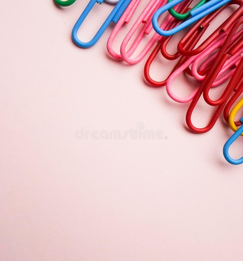 Mehrfarbige Büroklammern auf einem rosa Hintergrund Das Konzept ist Zeit zu schulen stockfoto