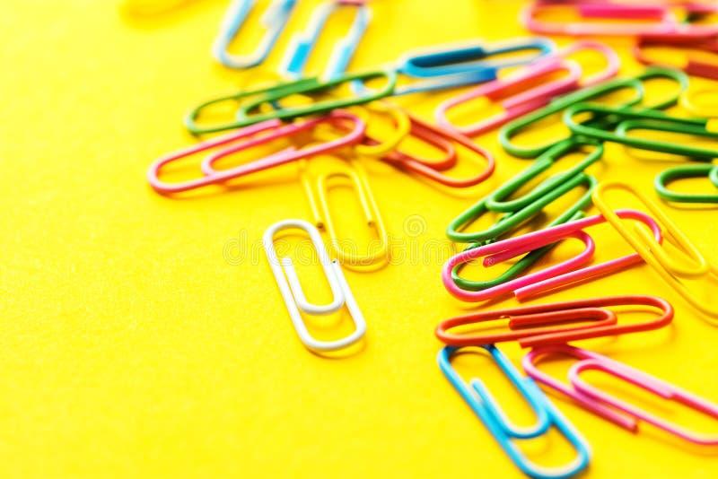 Mehrfarbige Büroklammern zerstreut auf hellen gelben Hintergrund Schulsekretariatsversorgungsschreibarbeitsdokumenten-Organisatio lizenzfreie stockbilder