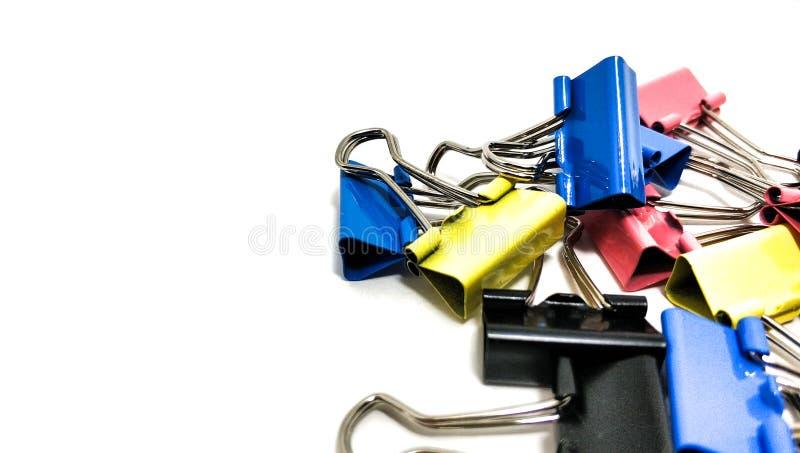 Mehrfarbige B?roklammern in einem Stapelabschlu? oben auf einem wei?en Hintergrund stockfotografie