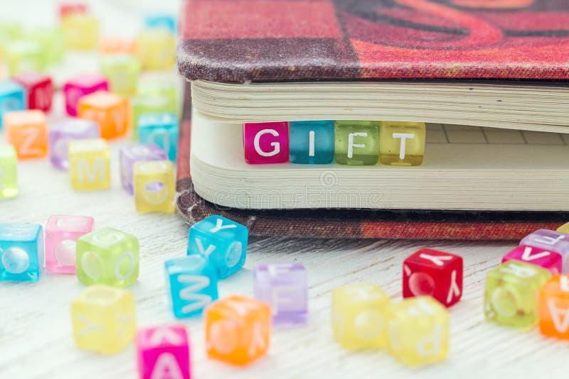 Mehrfarbige Blöcke mit dem Wort Geschenk stockbilder