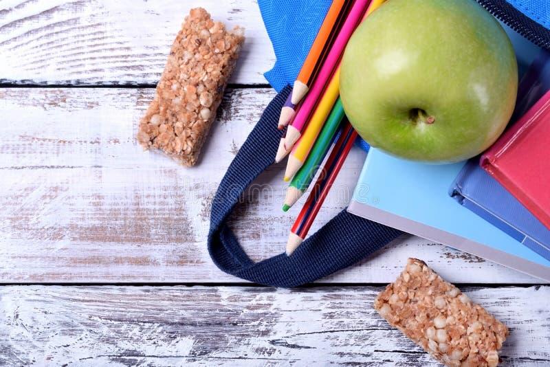 Mehrfarbige Bleistifte, Bücher, Apfel und Müsliriegel zerstreut aus dem Rucksack heraus stockfotografie