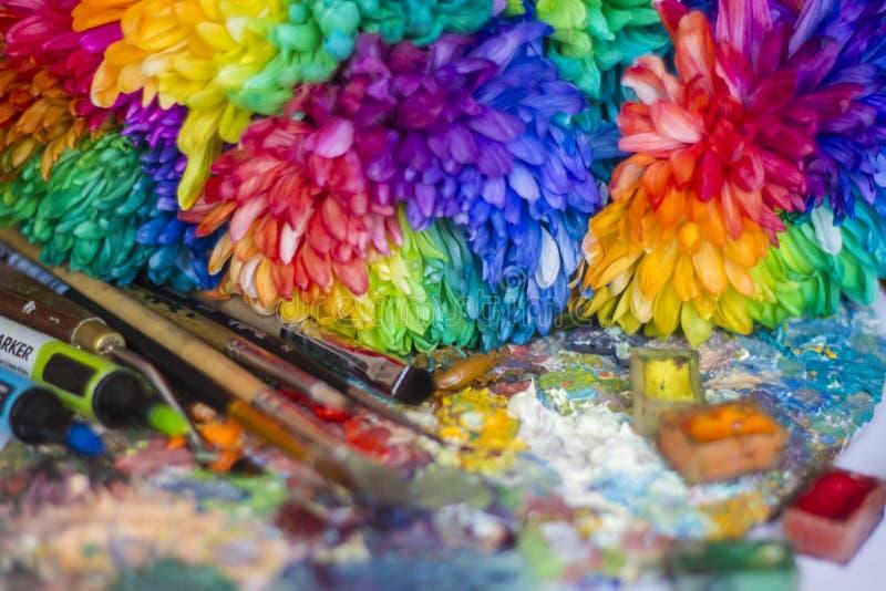 Mehrfarbige Chrysanthemen auf der Palette mit Farben und Bürsten des Künstlers lizenzfreies stockbild